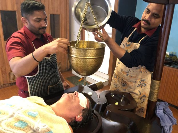 Me during the Shirodhara procedure being done by Joyal and Pradeep